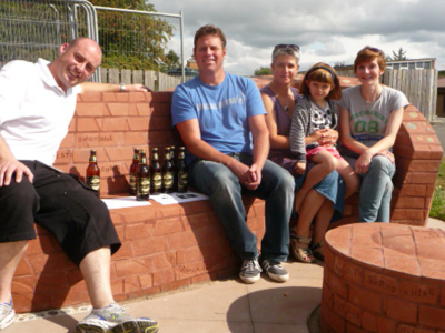 Completed bench with Stuart Dicken brick layer, Monty from Shropshire Radio, Ruth brick artists and daughter Jess with Cait Leach project manager