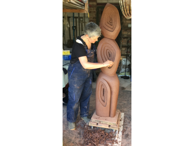 Carving garden sculpture in raw brick clay